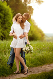 a man and a woman in love kissing on a pathway