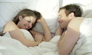 a couple laughing in bed