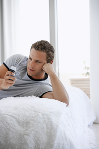a guy sending a text message to his girlfriend on a bed