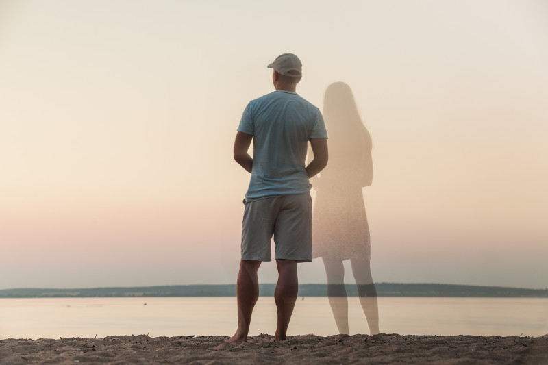 a man and a woman looking out to sea
