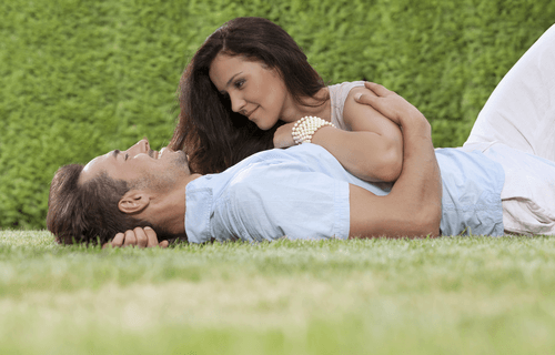 a man and woman lying on the grass holding each other