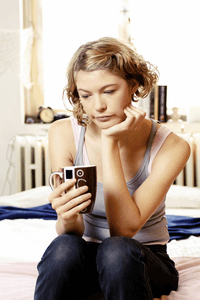 a woman sitting down with a cup of coffee reflecting about her ex boyfriend