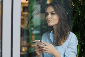a woman thinking of what to say in a text message