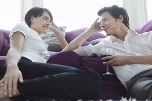 a couple having a conversation on the sofa while drinking wine