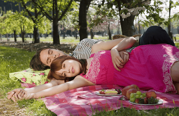 a couple laying on the grass together