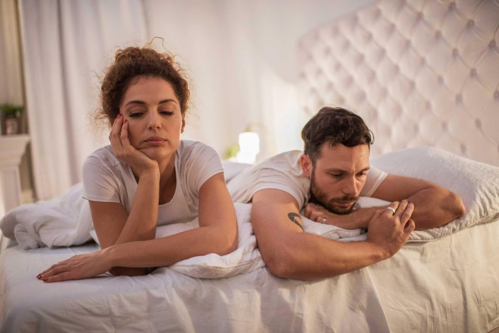 unhappy couple laying on a bed